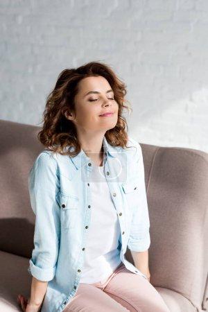 Photo pour Femme bouclée inspirée en chemise assise sur un canapé avec les yeux fermés sur le gris - image libre de droit