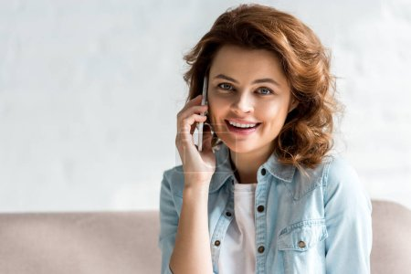 Photo for Pretty curly woman in shirt talking on smartphone with smile on grey - Royalty Free Image