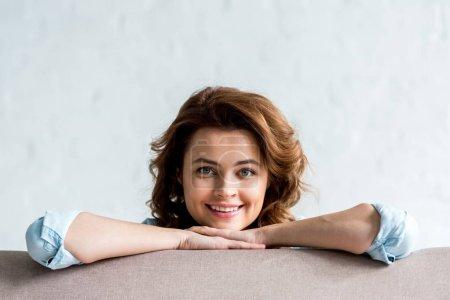 Photo pour Vue de face de souriante heureuse femme bouclée sur gris - image libre de droit