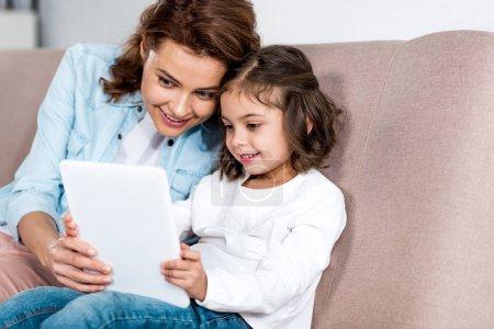 Photo pour Mère et fille souriantes assises sur un canapé brun et utilisant une tablette numérique - image libre de droit