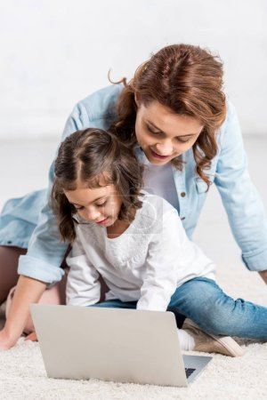 Photo pour Mère souriante et fille maternelle utilisant un ordinateur portable sur blanc - image libre de droit