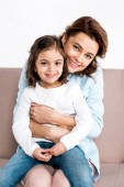 Laughing mother sitting on sofa and holding daughter on knees isolated on white