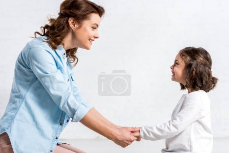 Photo for Smiling mother and daughter holding hands and looking at each other on white - Royalty Free Image