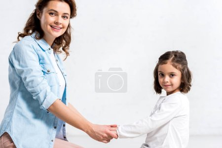Photo for Happy mother and kid holding hands and looking at camera on white - Royalty Free Image