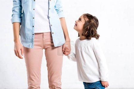 Częściowy widok kobiety w niebieską koszulę, trzymając się za ręce z córką na białym