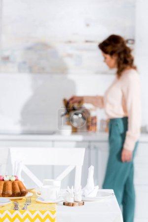 Photo pour Femme frisée avec bouilloire et table servi sur le premier plan - image libre de droit