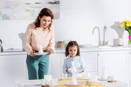 Photo for Curly mother and cute preschooler daughter serving table together - Royalty Free Image