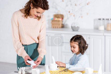 Photo pour Mère et fille souriantes pliantes serviettes blanches dans la cuisine - image libre de droit
