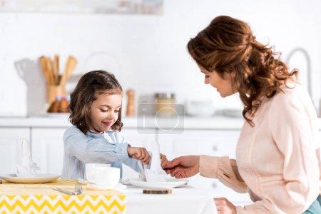 Photo pour Serviettes pliantes frisées mère et fille à table dans la cuisine - image libre de droit