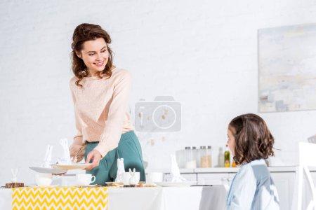 Photo pour Charmante femme regardant fille avec sourire tout en décorant la table - image libre de droit