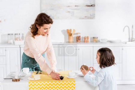 Photo for Cheerful curly mother and daughter serving table in kitchen - Royalty Free Image