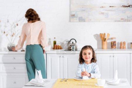 Photo pour Enfant joyeux assis à table et tenant une serviette blanche - image libre de droit