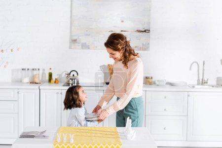 Photo pour Enfant d'âge préscolaire kid secourable mère pour définir la table dans la cuisine - image libre de droit