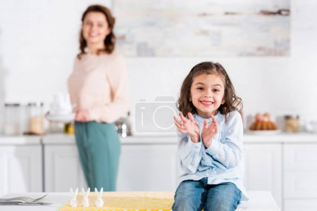 Photo for Joyful kid sitting on table and smiling in kitchen - Royalty Free Image