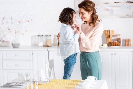 Photo pour Mère et enfant souriants dans la cuisine près de la table avec nappe jaune - image libre de droit