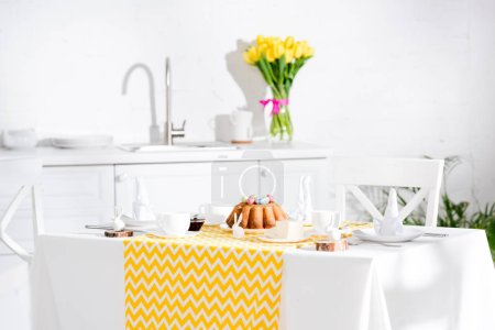 Photo for Served table with easter cake, napkins and ceramic bunnies in kitchen - Royalty Free Image