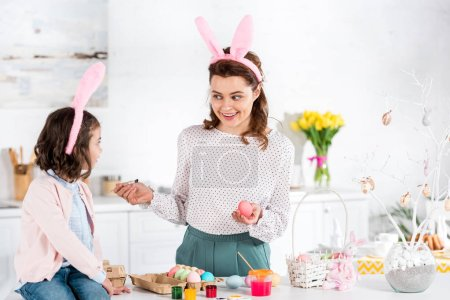 Photo for Smiling woman in bunny ears looking at daughter while painting easter egg in kitchen - Royalty Free Image