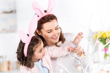 Foto de Feliz madre e hija en orejas de conejo adornando el árbol de Pascua juntos - Imagen libre de derechos