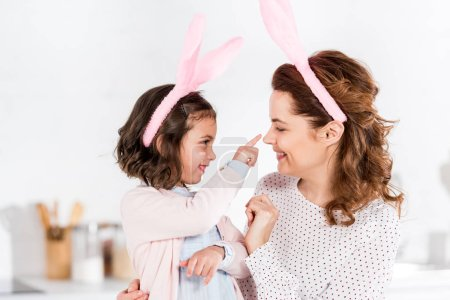 Photo for Mother and daughter in bunny ears playing and looking at each other - Royalty Free Image