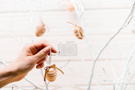 Photo for Cropped view of woman decorating easter tree with eggs - Royalty Free Image