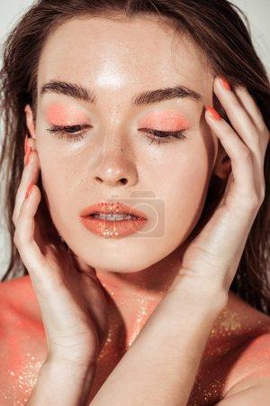 Foto de Hermosa mujer joven elegante con coral brillo maquillaje posando y tocar la cara - Imagen libre de derechos