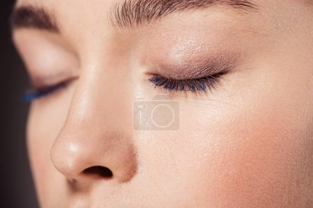 cropped view of woman with trendy make up posing with eyes closed