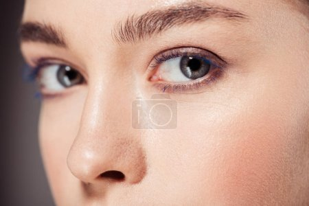 cropped view of beautiful woman with trendy make up looking at camera