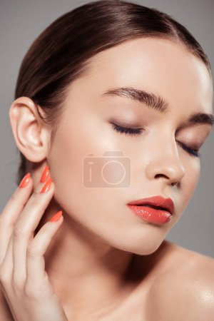 Photo for Beautiful stylish girl with eyes closed touching face and posing isolated on grey - Royalty Free Image
