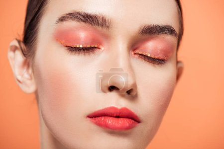 Photo for Beautiful trendy young woman with glitter makeup and eyes closed isolated on coral - Royalty Free Image