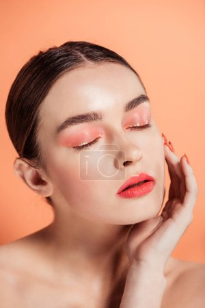 Photo for Beautiful stylish young woman touching face and posing with eyes closed isolated on coral - Royalty Free Image