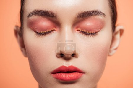 Photo for Beautiful stylish young woman with glitter makeup and eyes closed isolated on coral - Royalty Free Image