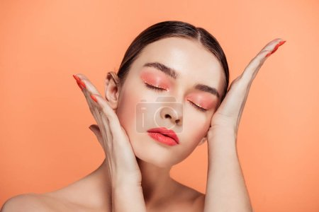 Photo for Beautiful stylish young woman touching face and posing isolated on coral - Royalty Free Image
