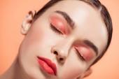 """Постер, картина, фотообои """"красивые стильные молодая женщина с блеск для макияжа и глаза закрыты, позирует, изолированные на Коралл"""""""
