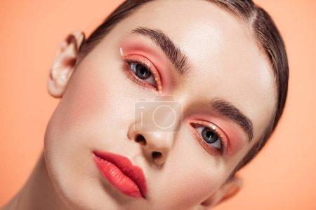Photo pour Belle jeune femme élégante avec maquillage paillettes regardant la caméra et posant coralliens isolés sur - image libre de droit