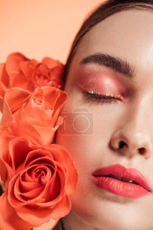 attractive stylish girl posing with rose flowers isolated on coral