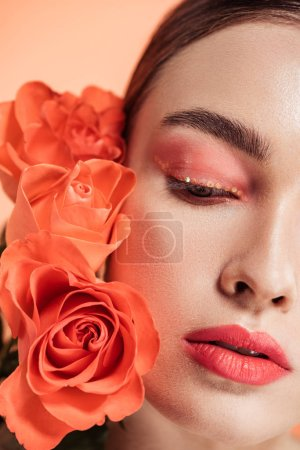 beautiful trendy girl posing with rose flowers isolated on coral