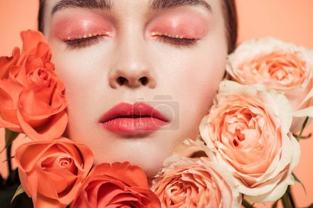 beautiful trendy girl posing with rose flowers and eyes closed isolated on coral