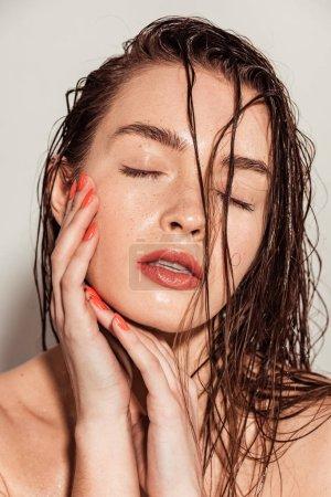 Foto de Hermosa mujer joven con los labios coral, ojos cerraron y húmedo pelo tocar cara sobre fondo gris - Imagen libre de derechos
