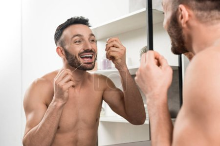 Photo pour Homme torse nu heureux regardant miroir tout en utilisant du fil dentaire dans la salle de bain - image libre de droit