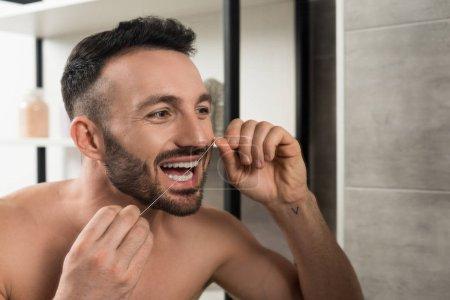 Photo pour Barbu homme torse nu regardant miroir tout en utilisant du fil dentaire dans la salle de bain - image libre de droit