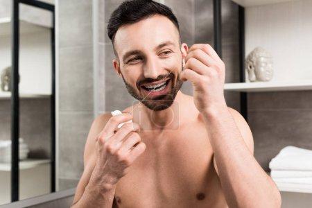 Photo pour Homme barbu en utilisant la soie dentaire tout en se tenant dans la salle de bain - image libre de droit