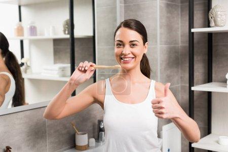 Photo pour Femme joyeuse montrant le pouce vers le haut tout en tenant la brosse à dents dans la salle de bain - image libre de droit