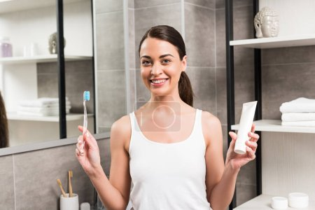 cheerful brunette woman holding toothbrush
