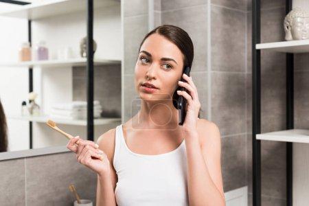 Photo pour Attrayant brunette femme tenant brosse à dents tout en parlant sur smartphone dans la salle de bain - image libre de droit