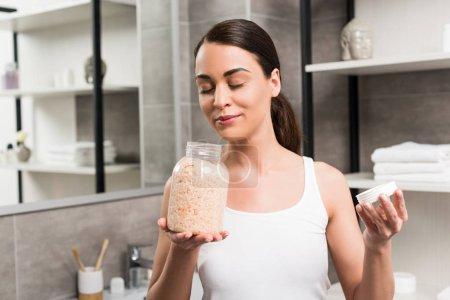Photo pour Jolie femme brune, odeur de sel de mer tout en tenant le bocal en verre dans la salle de bain - image libre de droit