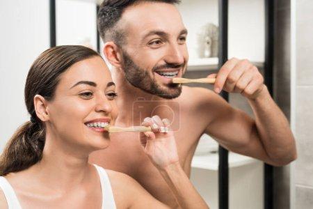 cheerful boyfriend and attractive girlfriend brushing teeth in bathroom