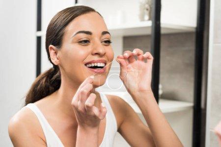 Photo pour Femme brune gaie utilisant du fil dentaire dans la salle de bain - image libre de droit