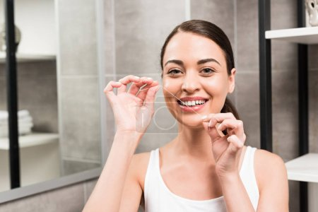 Photo pour Femme brune heureuse en utilisant du fil dentaire dans la salle de bain - image libre de droit