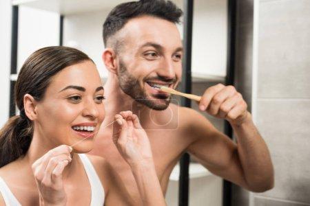 Photo pour Copain barbu brossant les dents près de petite amie en utilisant du fil dentaire dans la salle de bain - image libre de droit