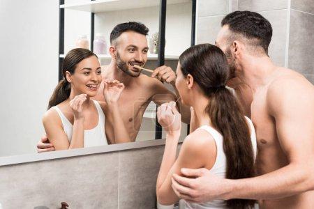 Photo pour Copain barbu brossant les dents près de petite amie à l'aide de fil dentaire tout en regardant miroir dans la salle de bain - image libre de droit